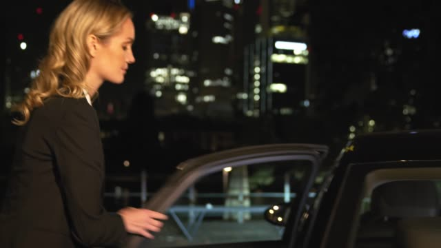 confident businesswoman boarding car at night - car park stock videos & royalty-free footage