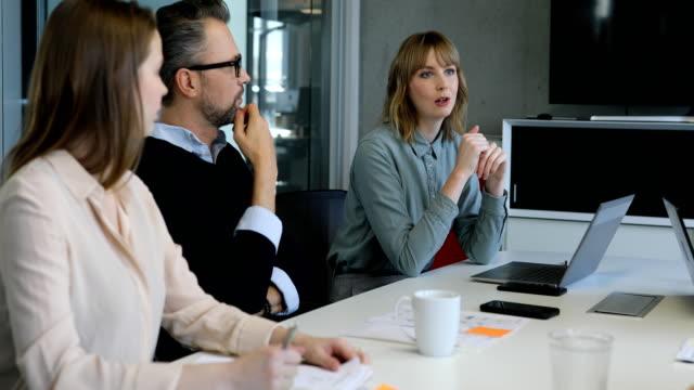 vídeos de stock, filmes e b-roll de mulher de negócios confiante, discutindo com os colegas - tempestade cerebral
