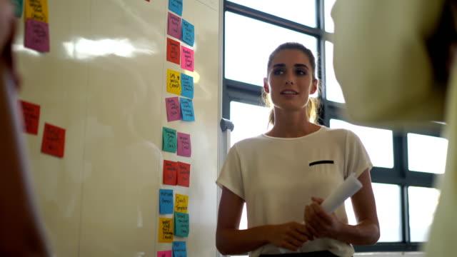 vidéos et rushes de confident businesswoman discussing with colleagues - petit groupe de personnes