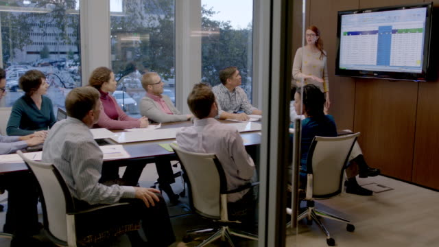 vídeos de stock, filmes e b-roll de confident businesswoman leads meeting in corporate boardroom, encourages round of applause (dolly shot) - informal para negócios