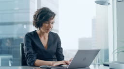 Confident Businesswoman Sitting at Her Desk and Working on a Laptop in Her Modern Office. Stylish Beautiful Woman Doing Important Job. In the Window Big City Business District View.
