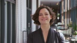 Confident businesswoman smiling outside auditorium