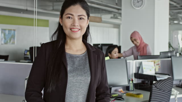 Confident businesswoman standing at desk in office