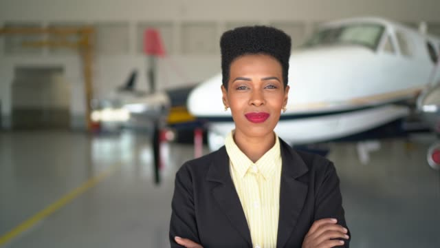 confident businesswoman standing in airport hangar with arms crossed - pardo brazilian stock videos & royalty-free footage