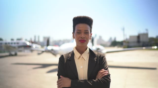 confident businesswoman standing in airport hangar with arms crossed - businesswoman stock videos & royalty-free footage
