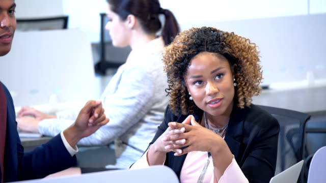 confident businesswoman talking to coworker in busy office - pacific islander stock videos & royalty-free footage