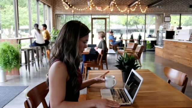 confident businesswoman telecommutes from trendy coffee shop - coffee cup stock videos & royalty-free footage