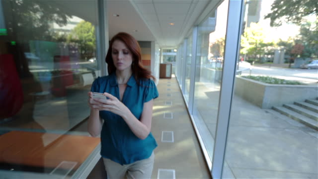 Confident businesswoman types on smart-phone as she walks briskly up long office hallway (tracking shot)