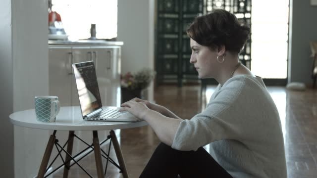 confident businesswoman using laptop in apartment - hemmakontor bildbanksvideor och videomaterial från bakom kulisserna