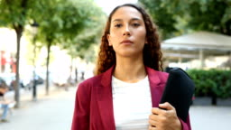 Confident businesswoman walking in the street
