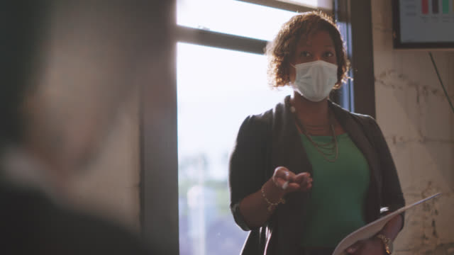 confident businesswoman wearing protective face mask gives presentation to employees in office - protective face mask stock videos & royalty-free footage