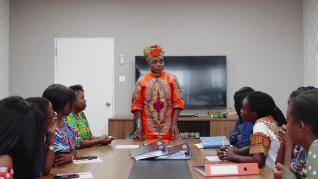 confident businesswoman wearing traditional chitenge chairing a business meeting - colleague help stock videos & royalty-free footage