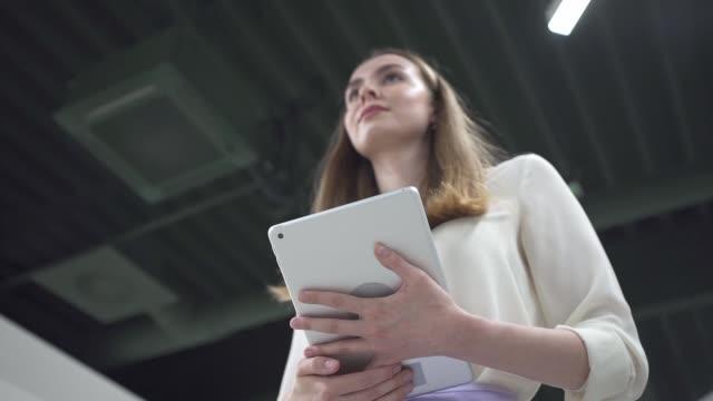 vidéos et rushes de femme d'affaires confiante avec une tablette numérique marchant dans le bureau - femme de pouvoir