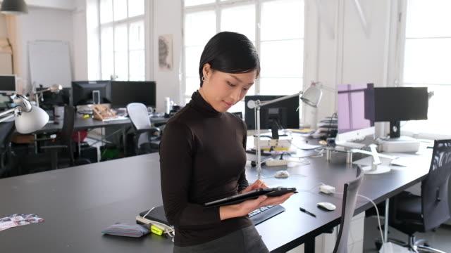 selbstbewusste geschäftsfrau mit digitalem tablet im büro - coworking stock-videos und b-roll-filmmaterial