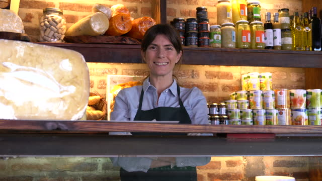 vídeos de stock e filmes b-roll de confident cheerful female business owner at a deli standing behind the refrigerator smiling at camera - laticínio