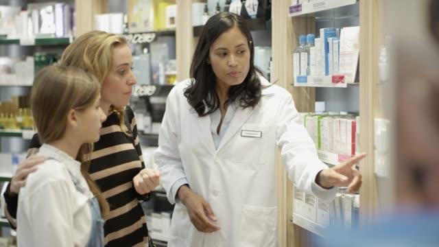 confident chemist explaining medicines to customers - pharmacist stock videos & royalty-free footage