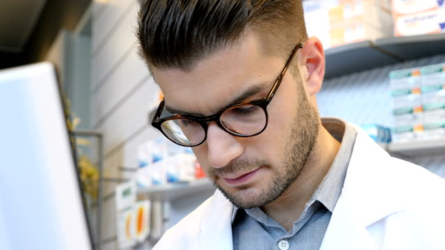 confident chemist using computer at pharmacy - pharmacist stock videos & royalty-free footage