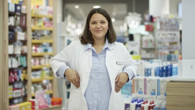 confident chemist with hands in pockets in store - shop assistant stock videos & royalty-free footage