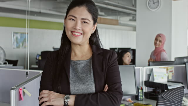 Confident Chinese businesswoman standing at desk in office