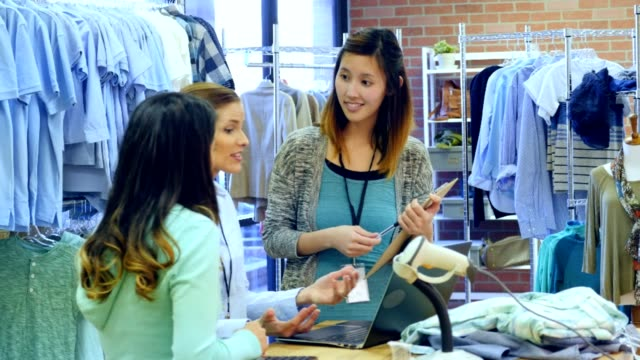 Confident clothing store owner or manager trains new employees
