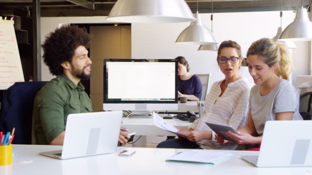 Confident coworkers discussing over digital tablet