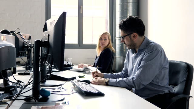 Confident coworkers using computers at office