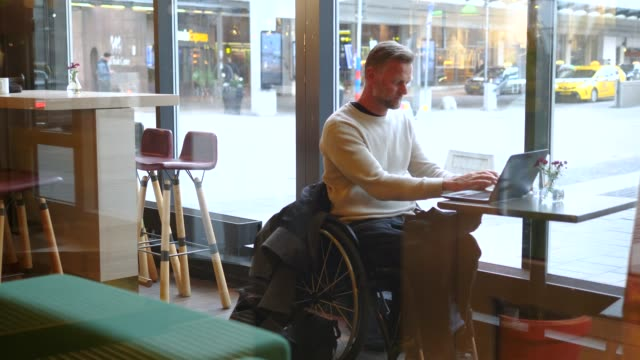 confident disabled mature businessman using laptop at table in hotel restaurant - 背景に人点の映像素材/bロール