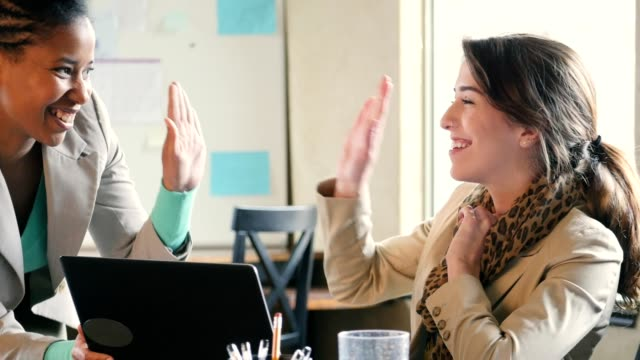 confident diverse businesswomen high five one another while discussing ideas - assistant stock videos and b-roll footage