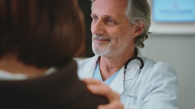 zuversichtlicher arzt diskutiert mit patient in klinik - arzt stock-videos und b-roll-filmmaterial