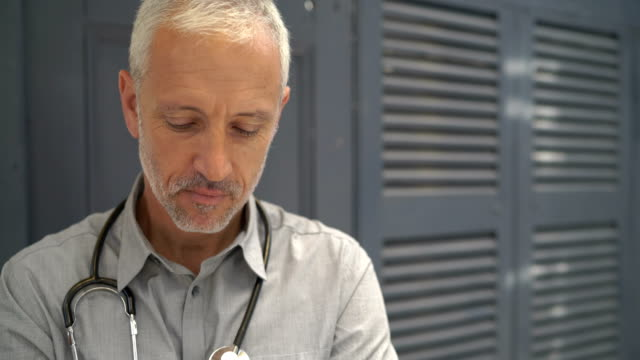 confident doctor with stethoscope in clinic - halbnahe einstellung stock-videos und b-roll-filmmaterial