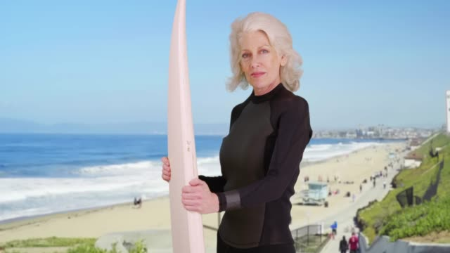 confident elder woman holding surfboard at the beach smiling at camera - wetsuit stock videos & royalty-free footage