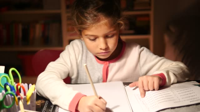 confident elementary girl writing in book at illuminated table - school supplies stock videos & royalty-free footage