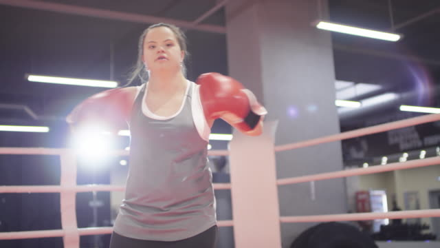 confident female boxer with down syndrome posing on ring - disability stock-videos und b-roll-filmmaterial