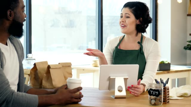 confident female coffee shop barista takes order from customer - gratuity stock videos & royalty-free footage