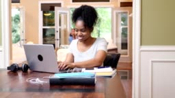 Confident female college student works on assignment at home