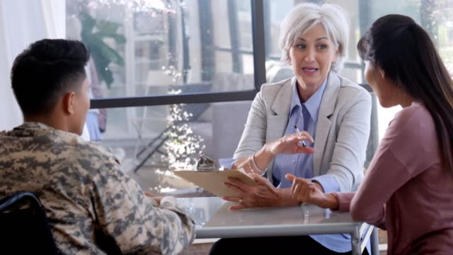 confident female counselor gives advice to military soldier in wheelchair - war veteran stock videos & royalty-free footage