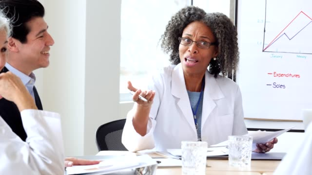 confident female doctor addresses hospital management and colleagues during meeting - lab coat stock videos & royalty-free footage