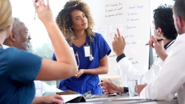 confident female doctor answers questions after presentation - braccia alzate video stock e b–roll