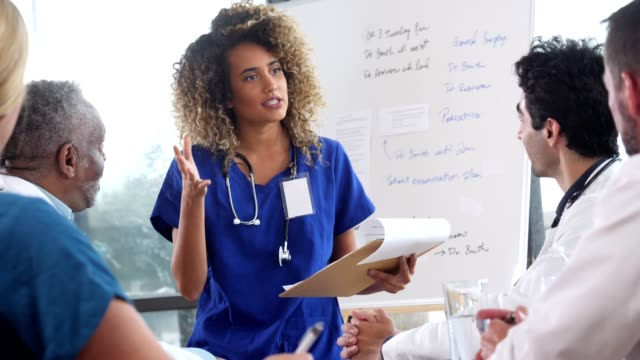 confident female doctor gives presentation during staff meeting - staff meeting stock videos & royalty-free footage