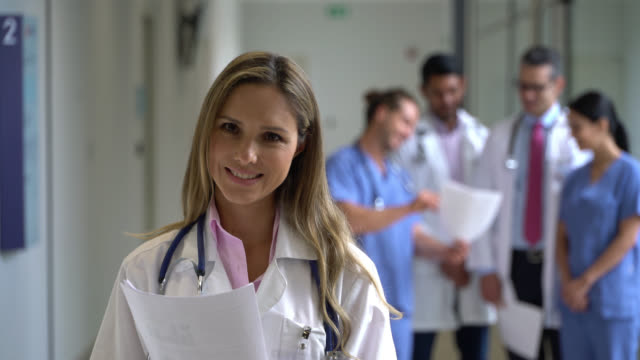 confident female doctor reading some documents and then smiling at camera while incidental healthcare workers stand at background - scrubs stock videos & royalty-free footage