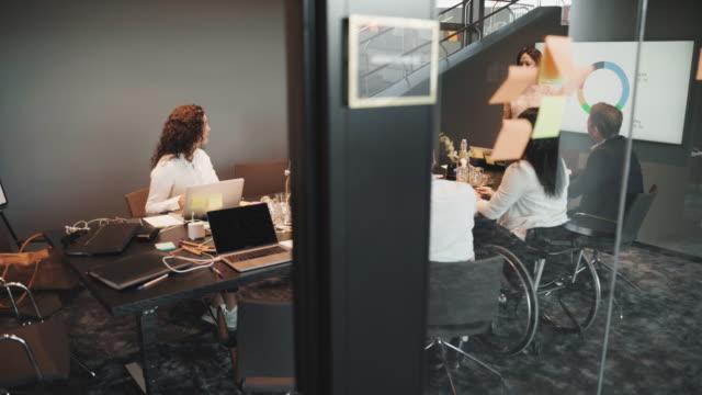 vídeos de stock, filmes e b-roll de confident female entrepreneur giving presentation while explaining strategy to colleagues in board room - sala de conferência