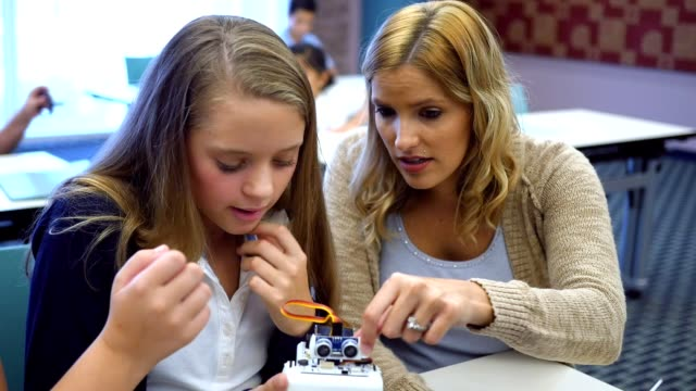 Confident female high school STEM teacher shows students how to program robot in technology class