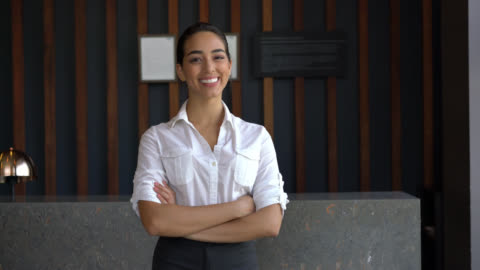 confident female hotel receptionist looking at camera smiling while crossing her arms - receptionist stock videos & royalty-free footage