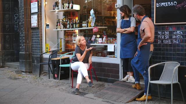 confident female mature owner talking to employees outside deli - vuxen bildbanksvideor och videomaterial från bakom kulisserna