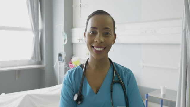 confident female nurse standing in hospital - focus on foreground stock videos & royalty-free footage