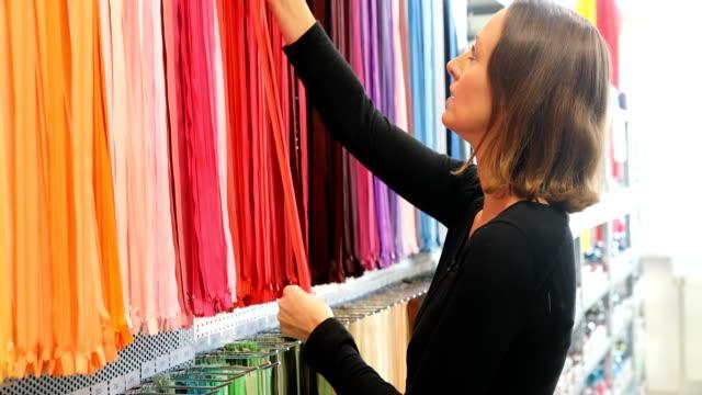 カラフルなジッパーを調べること自信を持って女性経営者 - ファッションデザイナー点の映像素材/bロール