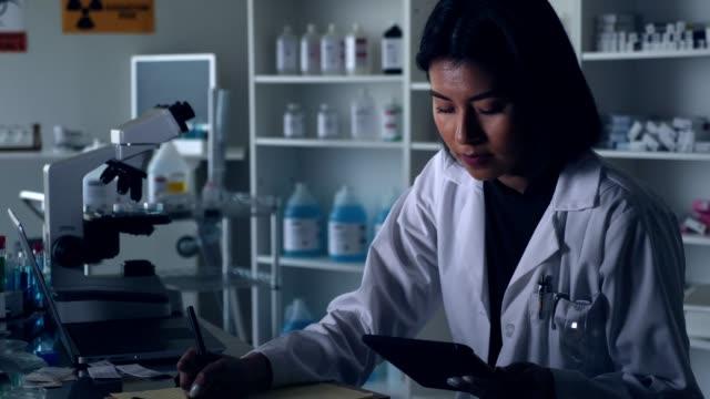 selbstbewusste wissenschaftlerin zeichnet beobachtungen in ihrem labor auf - portable information device stock-videos und b-roll-filmmaterial