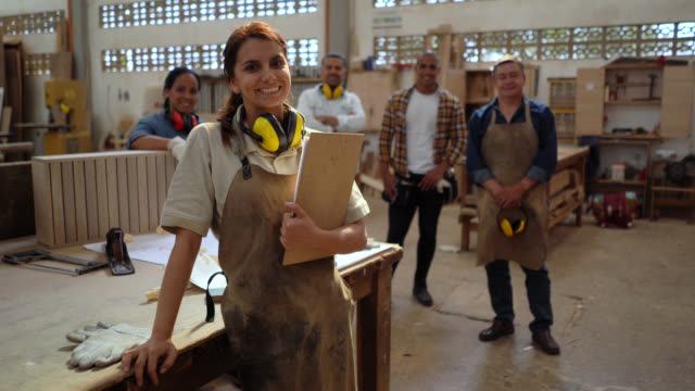 confident female supervisor of a carpentry holding a clipboard with her team standing behind all smiling at camera - carpentry stock videos & royalty-free footage