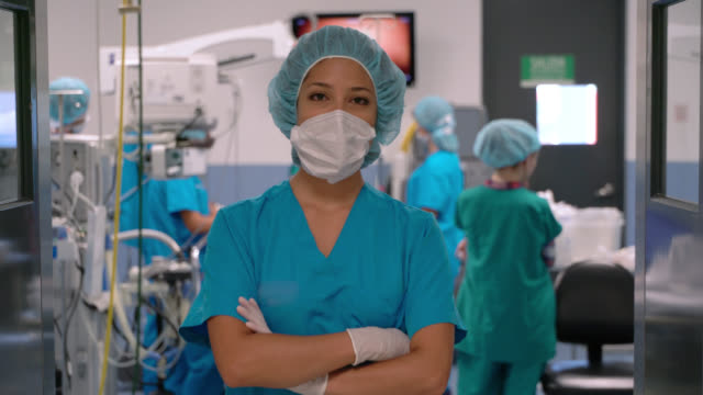 vídeos de stock e filmes b-roll de confident female surgeon wearing a protective mask while facing camera and crossing arms at a surgery room - auxiliar de saude