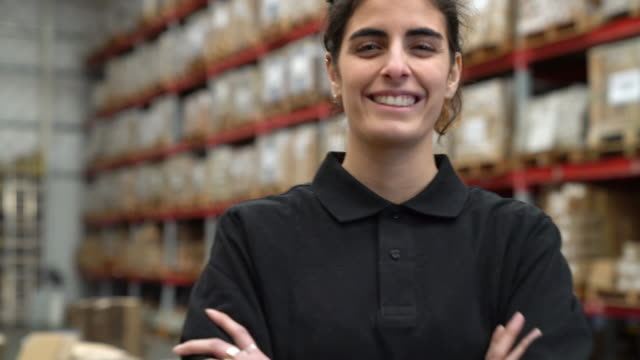 confident female worker smiling in warehouse - group of objects stock videos and b-roll footage